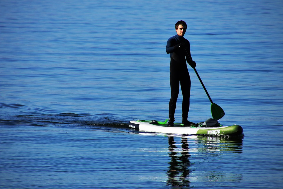 Man in a winter wetsuit on a SUP board
