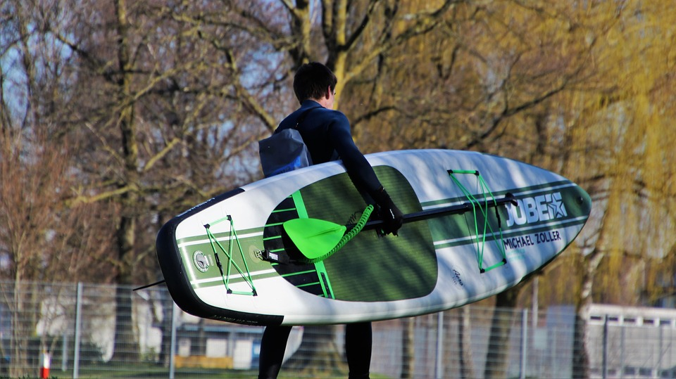 Man in a winter wetsuit carrying an SUP board