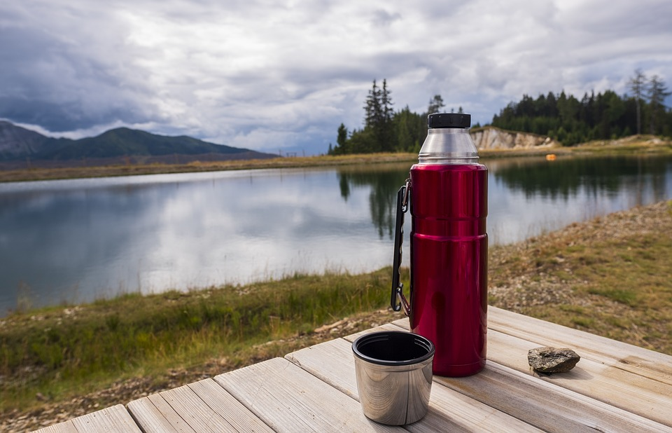 A Thermos flask on a bench overlooking a lake