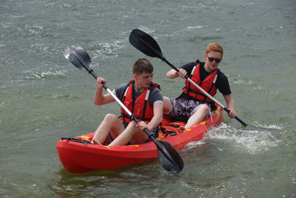 Two people on a two-seater sit on top kayak