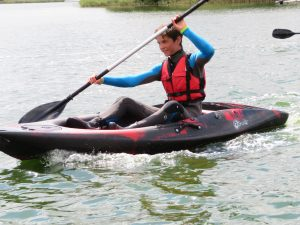 Young man using Riber kayak paddle on a sit on top kayak