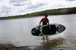 Man going into water with Riber iSUP board