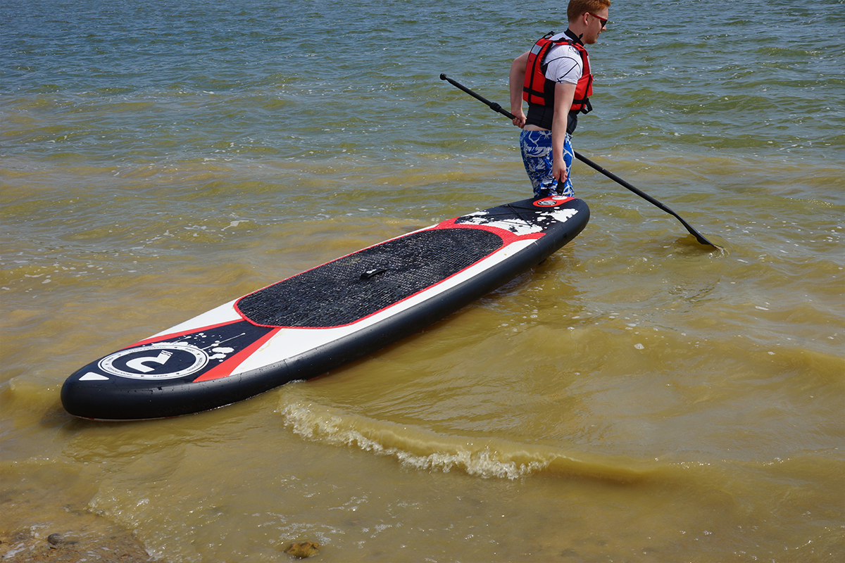 Man pulling a Riber SUP into water