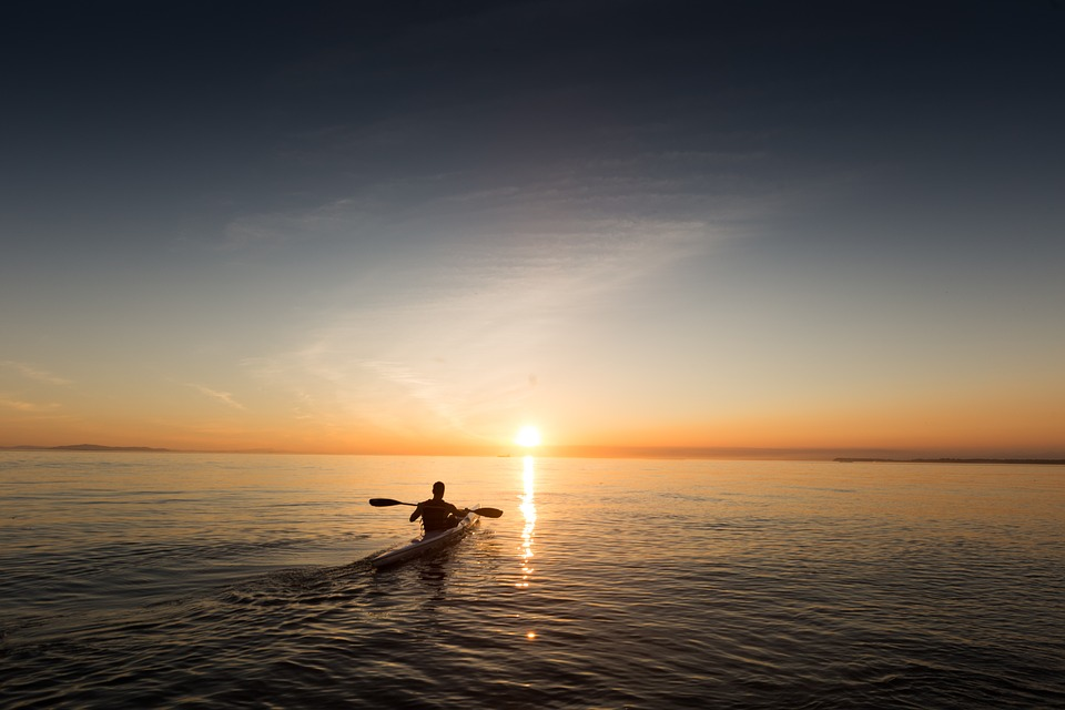 Person kayaking solo watching a sunset