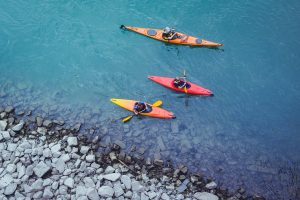 Three people kayaking by the shore