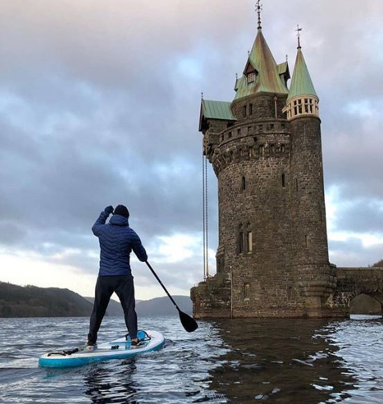 Person paddleboarding at  Lake Vyrnwy, Wales.
